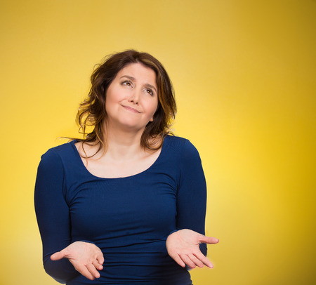 Closeup portrait dumb young woman, arms out asking whats problem, who cares so what, I dont know. Isolated yellow background space to right. Negative human emotion facial expressions,  body language