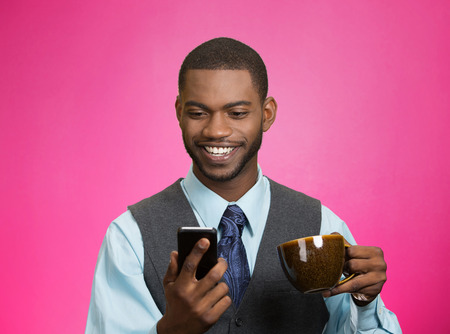 4g: Closeup portrait happy, smiling business man reading good news on smart phone, lawyer holding mobile, drinking cup coffee isolated pink background. Human face expression, emotion, corporate executive