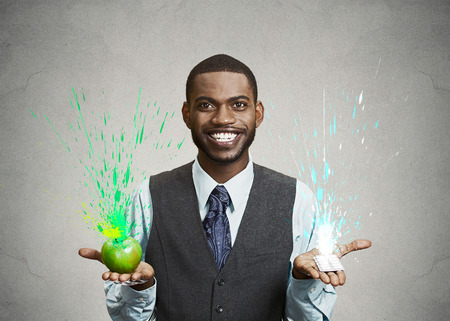 Closeup portrait young fit happy man holding green fresh apple in one hand, chewing gum in another, with colorful splashes coming out. Face expression, emotion. Fresh breath, good taste flavor concept photo