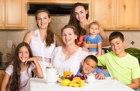 Groepsportret drie gelukkig generatie grote familie, grootmoeder, dochters, zonen, kleinkinderen klaar om het ontbijt in de keuken van hun huis op moederdag hebben. Positieve gezicht uitdrukkingen, emoties Stockfoto