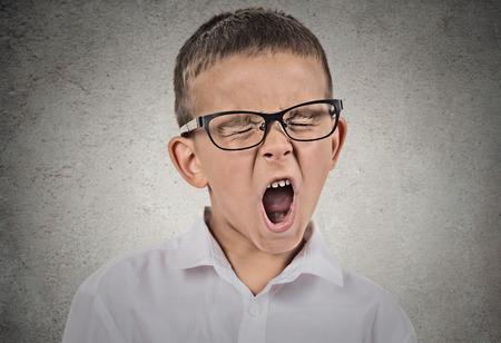 bored man: Ritratto del primo piano bambino stanco con occhiali sbadigli, isolato su sfondo grigio muro. Le espressioni facciali umane, le emozioni, i sentimenti, il linguaggio del corpo. Lunghe ore di scuola, concetto giornata intensa.