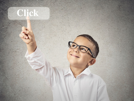 Closeup portrait happy, smiling boy, child with glasses pushing Click button on touch screen display, isolated grey wall background. Positive face expressions, emotions. Social media, internet concept photo