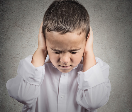 Closeup portrait, headshot child, boy covering ears with hands, doesnt want to hear loud noise, conversation isolated grey wall background. Human face expression, emotion, feeling reaction perception