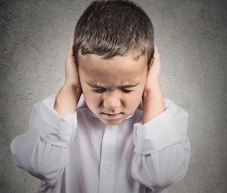 Primer retrato, tiro en la cabeza del niño, niño que cubra las orejas con las manos, no quiere oír ruidos fuertes, conversación aislado fondo de la pared gris. Expresión de la cara humana, la emoción, la percepción reacción sintiendo Foto de archivo - 30923940