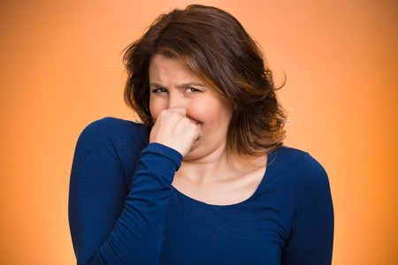 Closeup portrait middle aged woman who covers, pinches her nose with hand looks with disgust, something stinks, bad smell, situation, isolated orange background. Human face expressions, body language photo