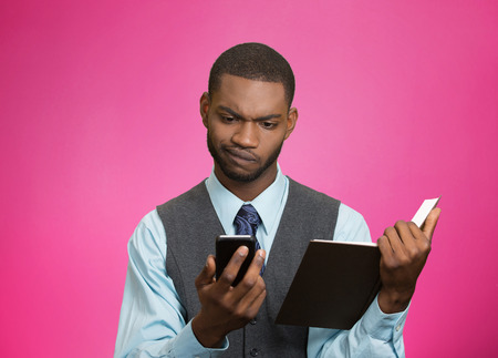 business skeptical: Closeup portrait confused, skeptical business man, executive reading news on smart phone, holding book isolated pink background. Human face expression, emotion, body language, corporate lifestyle