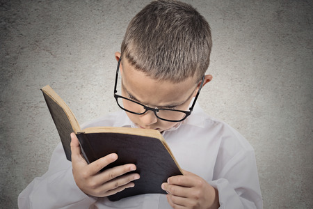 Close up portrait young, little man with glasses holding, reading old book, having difficulty to see text isolated grey wall background. Face expression. Education concept. Vision problems in children