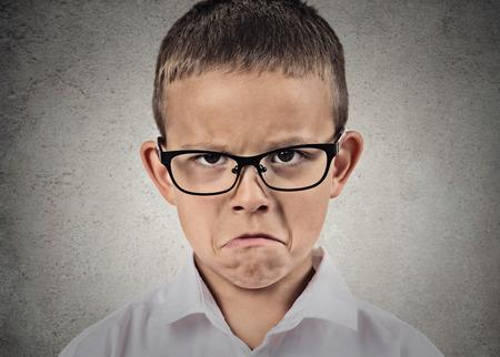 Retrato del primer infeliz, triste, niño, muchacho de mirada divertido con la camisa blanca, con gafas aislado fondo de la pared gris. Emociones humanas negativas, las expresiones faciales, los sentimientos, la percepción vida, reacción