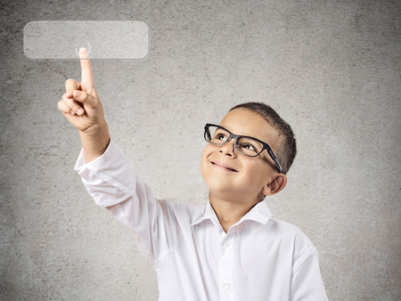 Closeup portrait happy boy with glasses pushing digital button with copy space, isolated grey wall background. Positive emotions, feelings, facial expressions. New technology concept. photo