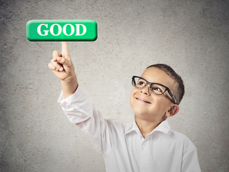 grades: Quality control. Boy hand press good button. Happy, smiling child with glasses clicks green icon on touch screen display, isolated grey wall background. Positive face expression, emotions, perception