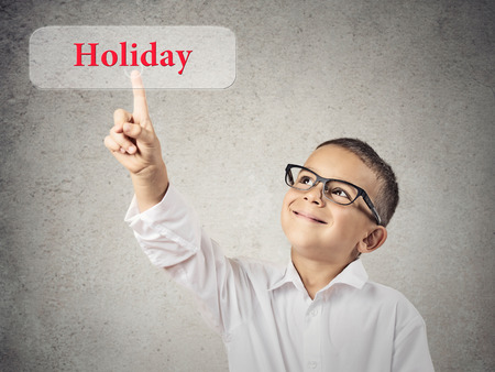 Closeup portrait happy, smiling handsome boy, child clicking on Holiday button, isolated grey wall background. Vacation, travel, leisure concept. Positive facial expression, emotions, life perception photo