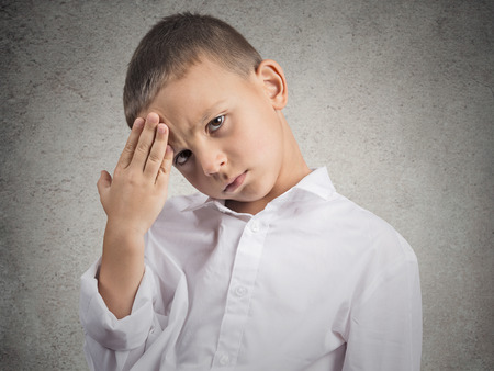 Young man suffering from headache. Closeup portrait little boy having a head ache, isolated grey wall background. Negative human face expressions, emotions, feelings, body language, life perception photo