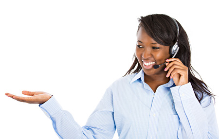 customer service phone: Closeup portrait beautiful smiling female customer representative with phone headset pointing at copy space with hand isolated white background. Positive human emotions, facial expressions, attitude Stock Photo