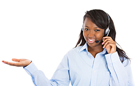 Closeup portrait beautiful smiling female customer representative with phone headset pointing at copy space with hand isolated white background. Positive human emotions, facial expressions, attitude Standard-Bild