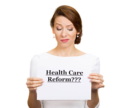 health reform: Portrait skeptical female, citizen, professional, doctor, holding sign health care reform isolated white background. Medicaid, legislation debate insurance plan coverage concept Stock Photo