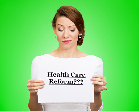 price uncertainty: Portrait skeptical female, citizen, professional doctor holding sign health care reform with question isolated green background. Medicaid, legislation debate insurance plan coverage concept