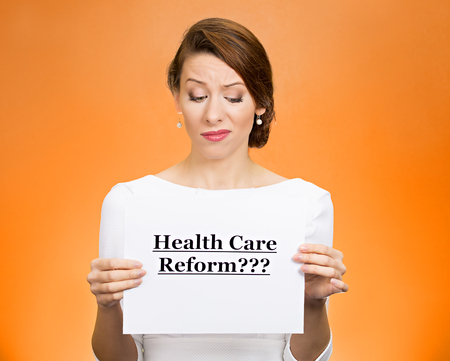 price uncertainty: Portrait skeptical female, citizen, professional, doctor, holding sign health care reform isolated orange background. Medicaid, legislation debate insurance plan coverage concept.