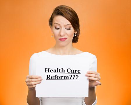 Portrait skeptical female, citizen, professional, doctor, holding sign health care reform isolated orange background. Medicaid, legislation debate insurance plan coverage concept.
