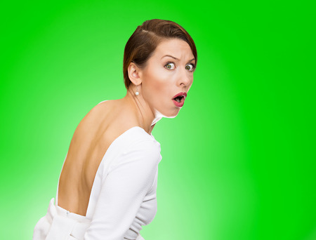 Closeup portrait, young, scared, afraid, woman, citizen, employee, full of fear on run, chased by someone, isolated green background. Human face expressions, emotions, reaction, feelings, attitude photo