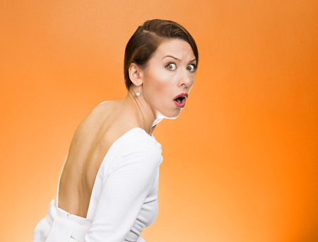 chased: Closeup portrait, young, scared, afraid, woman, citizen, employee, full of fear on run, chased by someone, isolated orange background. Human face expressions, emotions, reaction, feelings, attitude Stock Photo