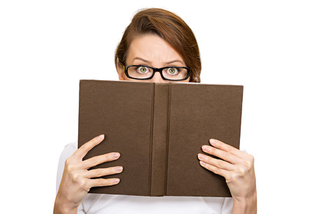 socially: Closeup portrait woman with glasses hiding her face behind book, looking at camera suspicious, isolated white background. Education concept. Face expression, life perception. Girl holding book