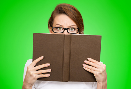 introvert: Closeup portrait woman with glasses hiding her face behind book looking at camera suspicious isolated green background. Education concept. Life perception. Girl holding book, scared face expression Stock Photo