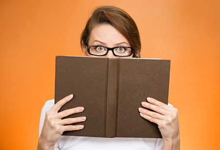 face expression: Closeup portrait woman with glasses hiding her face behind book, looking at camera suspicious, isolated orange background. Education concept. Face expression, life perception. Girl holding book