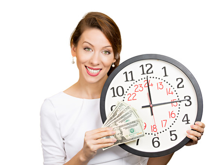 debt goals: Closeup portrait happy young business woman, corporate employee, ceo holding wall clock, dollar bills in hands. Time is money concept isolated white background. Positive human emotions face expression