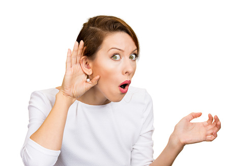 hearsay: Closeup portrait young nosy woman hand to ear gesture, trying carefully intently secretly listen in on juicy gossip conversation news privacy violation isolated white background. Human face expression Stock Photo