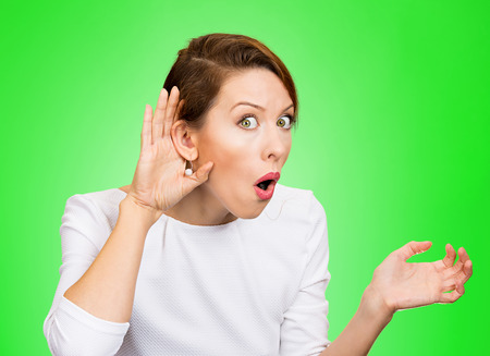 chitchat: Closeup portrait young nosy woman hand to ear gesture trying carefully intently secretly listen in on juicy gossip conversation news privacy violation isolated green background. Human face expression