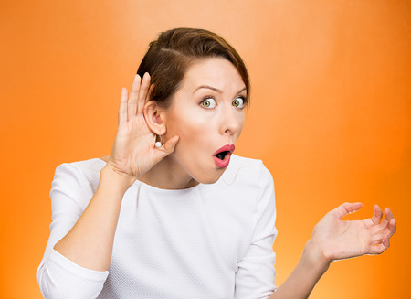 intrusive: Closeup portrait young nosy woman hand to ear gesture trying carefully intently secretly listen in on juicy gossip conversation news privacy violation isolated orange background. Human face expression