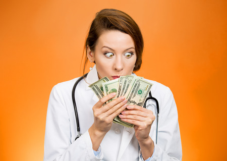 reimbursement: Closeup portrait greedy, miserly health care professional, female doctor holding looking at her money dollars in hand, fascinated isolated orange background. Negative human emotion, facial expressions Stock Photo
