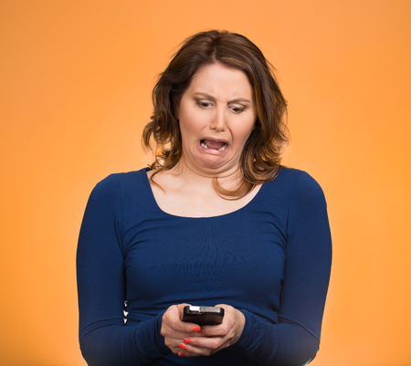 inappropriate: Upset woman holding cellphone, disgusted shocked with message she received isolated orange background. Funny looking human face expressions, emotion, feelings, reaction life perception, body language Stock Photo