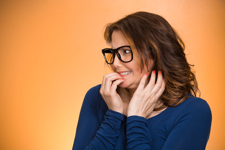 insecure: Closeup portrait nervous woman with glasses biting her fingernails craving something, anxious isolated orange background copy space. Negative human emotion facial expression body language perception