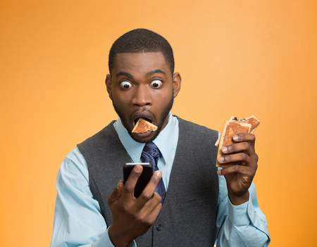 Portrait surprised, funny looking, corporate business man holding, reading bad news on smart phone, eating cookie about to choke isolated orange background. Face expression emotion unexpected reaction photo
