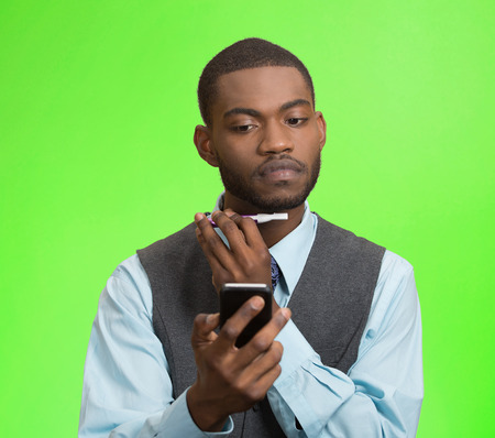 simultaneous: Portrait serious young business man shaving his face, using trimmer texting, reading news on smart phone isolated green background. Human face expression busy life of corporate executive. Multitasking