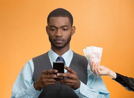 cash back: Executive business man texting, reading news, e-mail on smart phone, ignoring offered money, cash back, isolated orange background. Human facial expression emotion, feeling perception. Phone addiction