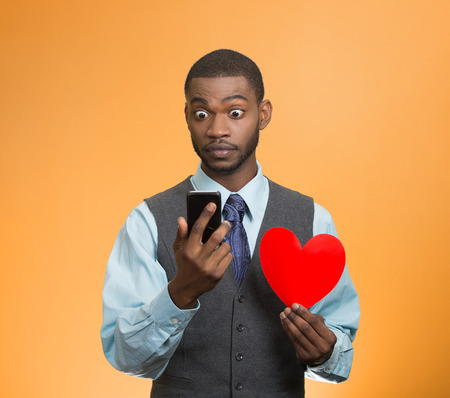 Portrait shocked young man, guy reading breaking news on smart phone holding red heart in his hand isolated orange background. Human facial expression emotion feeling body language unexpected reaction photo
