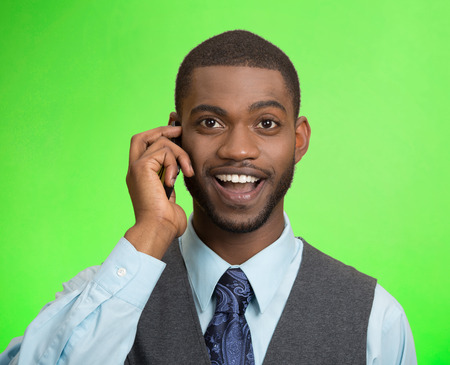 Headshot, portrait happy business man, young guy talking on mobile phone, isolated green background. Positive human facial expressions, emotions, feelings, life perception, attitude, thinking photo