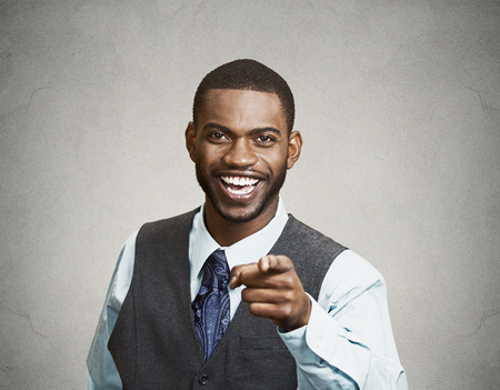 fullness: Closeup portrait happy young man, laughing, pointing with finger at someone, something, isolated grey wall background. Positive human face expressions emotion, feelings, attitude, approach, perception