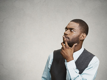 wonder: Side view portrait young, puzzled business man thinking, deciding about something, finger on lips, looking up, confused isolated grey wall background with copy space. Emotion facial expression feeling