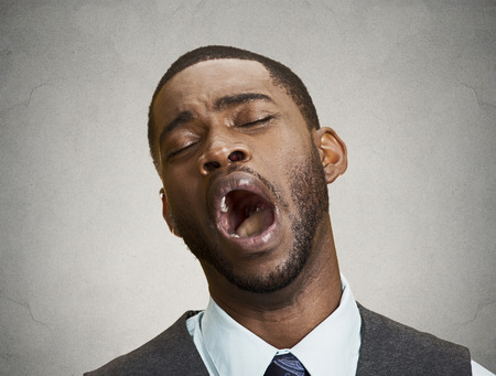 blase: closeup portrait, headshot young bored man, yawning isolated grey wall background. Facial expressions, feelings, body language. Long working hours, chronic fatigue of corporate executive Stock Photo