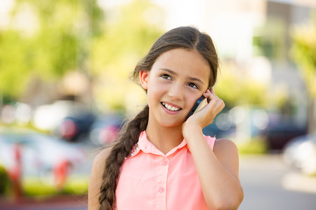 Closeup portrait, happy teenage girl talking on cell, mobile phone, isolated outdoors, outside background. Positive human emotions, facial expressions, life perception, communication concept photo