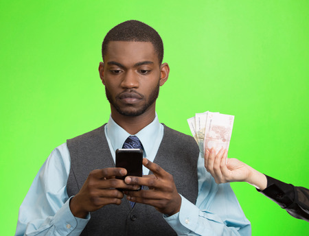 cash back: Executive business man texting, reading news, e-mail on smart phone, ignoring offered money, cash back, isolated green background. Human facial expression emotion, feeling perception. Phone addiction
