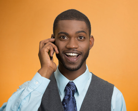 Headshot, portrait happy business man, young guy talking on mobile phone smiling isolated orange background. Positive human facial expressions, emotions, feelings, life perception, attitude, thinking photo