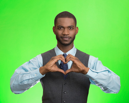 Closeup portrait handsome smiling young business man makes the heart using fingers, hands, isolated green background. Positive human emotions, facial expressions, feelings, body language, attitude photo