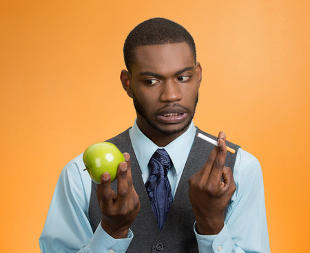 Portrait headshot executive businessman trying decide on healthy life choices, holding craving cigarette versus green apple isolated orange background. Face expression, body language, bad human habits photo