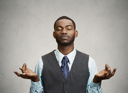 business stress: Young businessman meditating, eyes closed, isolated grey wall background. Stress relief techniques at work concept. Take a deep breath.
