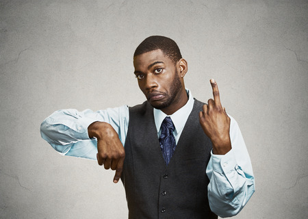 ambiguous: Portrait confused young business man pointing in two different directions, not sure which way to go in life, hesitant to make decision isolated grey background. Emotion facial expression body language
