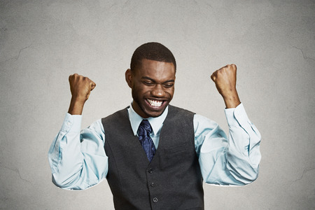 enrolled: Closeup portrait happy successful student, business man winning, fists pumped celebrating success isolated grey wall background. Positive human emotion, facial expression. Life perception, achievement